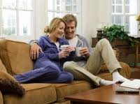 An elderly couple talks about getting pregnant after 40 as they sit on their sofa and drink their coffee.